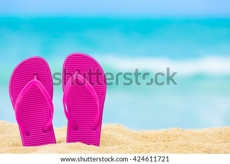 Pair of sandals on the beach. - stock photo