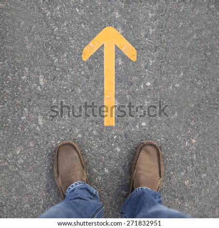 Pair of shoes on a road with yellow arrow - stock photo