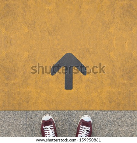Pair of shoes standing on a road with grey arrow on the yellow background - stock photo