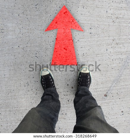 Pair of shoes standing on a road with red arrow on concrete background - stock photo