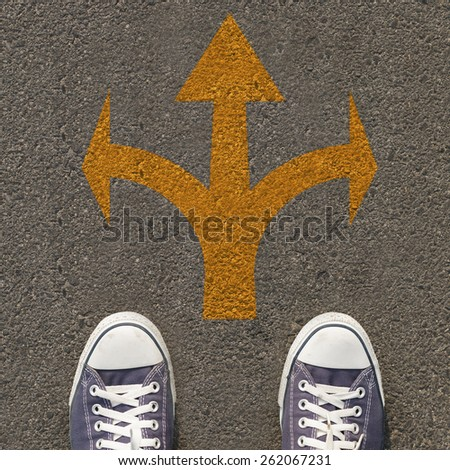 Pair of shoes standing on a road with three yellow arrow - stock photo