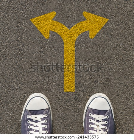 Pair of shoes standing on a road with traffic sign - stock photo