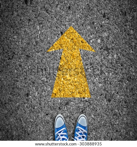 Pair of shoes standing on a road with yellow arrow on asphalt background - stock photo