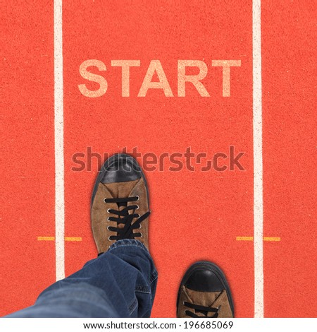 Pair of shoes standing on running track background with START - stock photo
