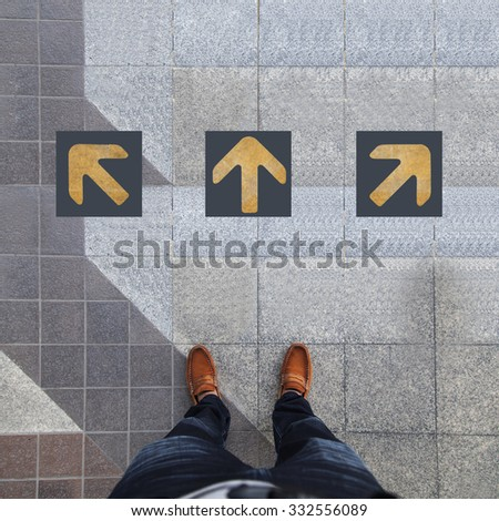 Pair of shoes standing with three yellow arrow - stock photo
