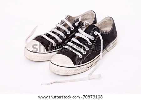 Pair of shoes worn with the laces loose over white background - stock photo