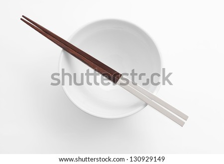 Pair of silver handled chopsticks resting on an empty white bowl. Soft shadow and isolating clipping path.