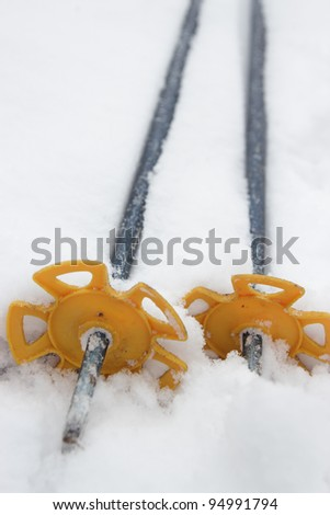 Pair of ski and hiking poles on white snowy background. Shallow depth of field - stock photo