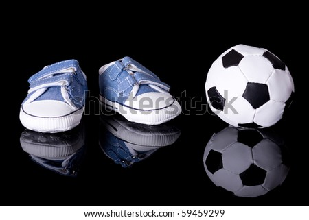 pair of small baby shoes next to football ball, footballer baby or baby footballer concept, studio shoot isolated on black with reflection - stock photo