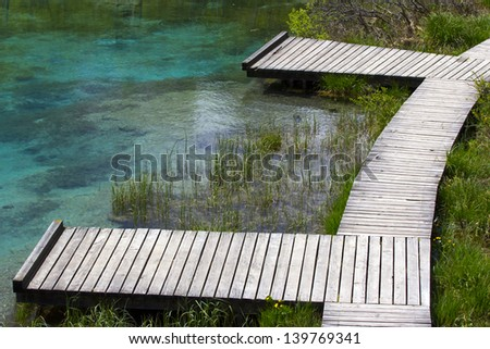 Pair of small wooden piers by the lake. - stock photo