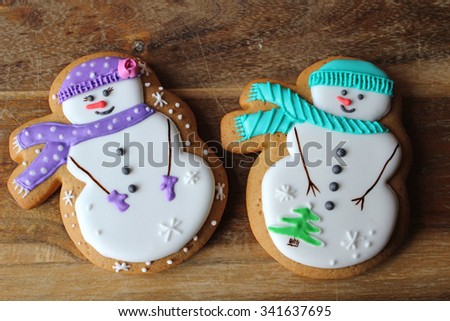 Pair of snowmen gingerbread cookies decorated with glaze on the wooden background