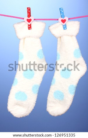 Pair of socks with polka dots hanging to dry over blue background