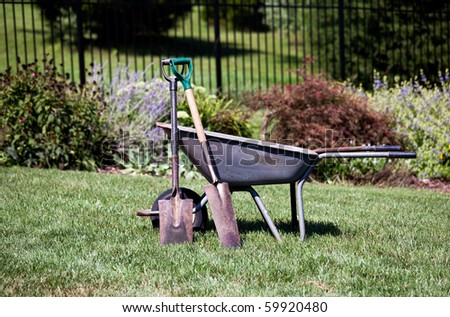 Pair of spades resting against a wheelbarrow in a flower filled back garden - stock photo