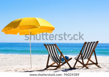 Pair of sun loungers and a beach umbrella on a deserted beach; perfect vacation concept - stock photo