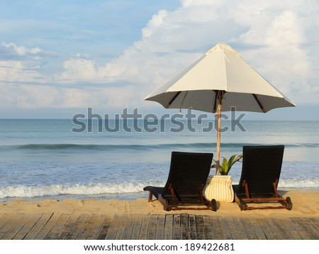 Pair of sun loungers and a beach umbrella on the beach  - stock photo