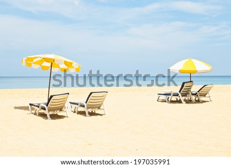 Pair of sun loungers and a beach umbrellas on the beach - stock photo