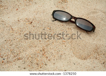 Pair of sunglasses sitting in the sand at the beach - stock photo