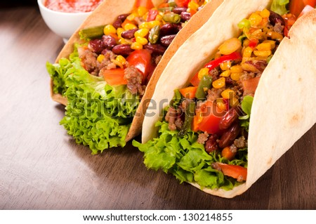 Pair of tacos on the wooden table - stock photo
