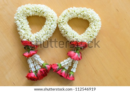 pair of thai style white and red flower garland in heart shape on wood background - stock photo