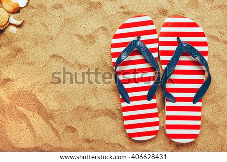 Pair of thongs or flip flops on beach sand, top view of summer holiday vacation accessories - stock photo