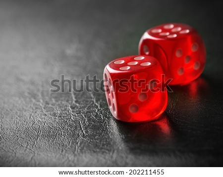 Pair of thrown red dices on black background - stock photo