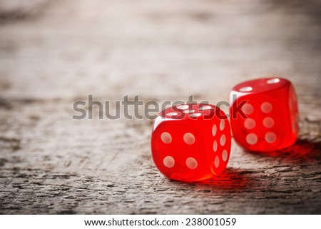 Pair of thrown red dices on old wooden table - stock photo