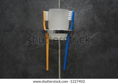 Pair of Toothbrushes in a holder with a glass. - stock photo