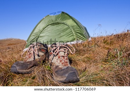 pair of touristic boots near a tent - stock photo
