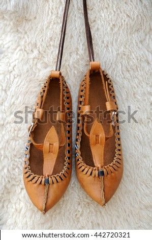 Pair of traditional Bulgarian leather shoes against white lambskin background