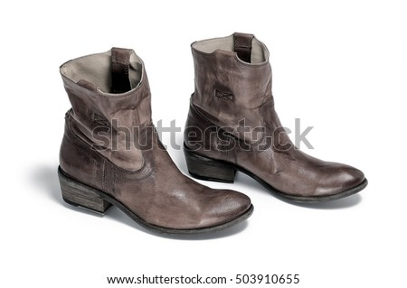 Pair of traditional cowboy boots on a light background. Retro and dark toning of the image