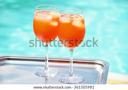 Pair of traditional Italian Aperol Spritz cocktails at the swimming pool
