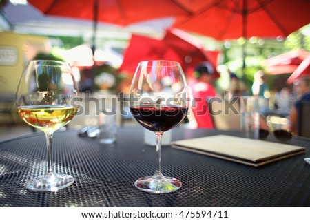 Pair of two wine glasses with red pinot noir and white chardonnay on a beautiful patio dining table outdoors under umbrellas in the summer