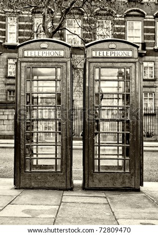 Pair of typical London phone booths in black and white