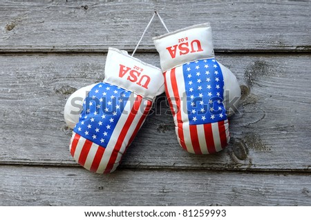 Pair of used boxing gloves on the nail against thw wooden wall background - stock photo