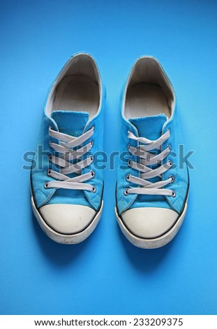 Pair of used gym shoes on blue - stock photo