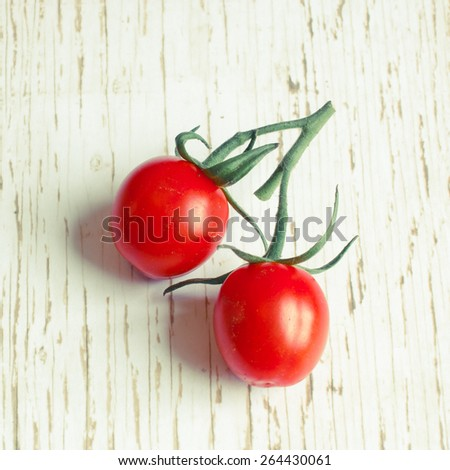 Pair of vine tomatoes on a wooden surface with retro filter applied - stock photo