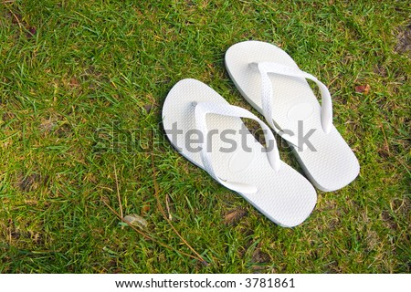 pair of white flipflops in grass background - stock photo