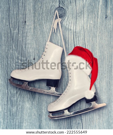 Pair of White Ice Skates and Santa Claus hat - background on vintage, retro style.  - stock photo