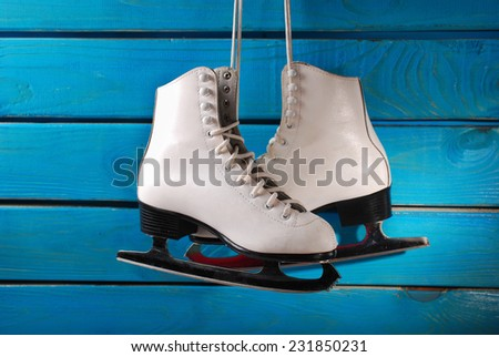 pair of white ice skates for girl hanging on blue wooden background - stock photo