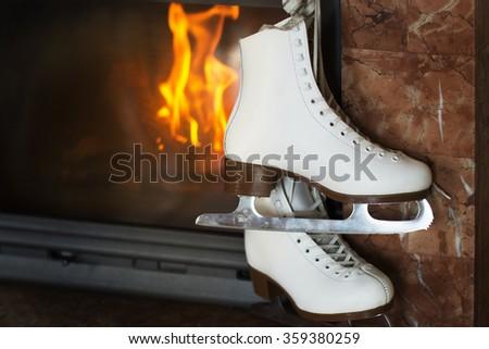 Pair of white skates near the fireplace - stock photo