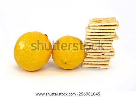pair of whole lemons with stack of soda crackers isolated on white background - stock photo