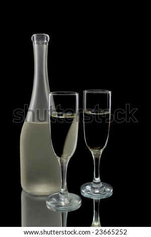 Pair of wine flutes and wine bottle against a black background - stock photo