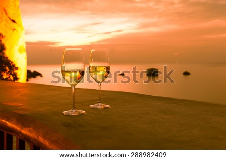 Pair of wine glasses in a beautiful ocean view setting.  - stock photo