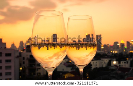 Pair of wine glasses on a city roof top.  - stock photo