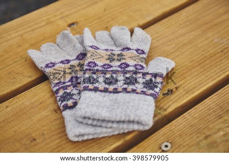 Pair of winter gloves on wooden table - stock photo