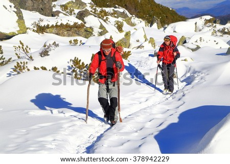 Pair of winter mountaineers on sunny trail across snow covered valley - stock photo