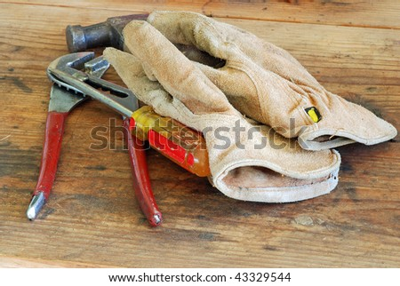 Pair of worn leather gloves with claw hammer, channel lock pliers and screwdriver laying on top of a weathered work bench. - stock photo