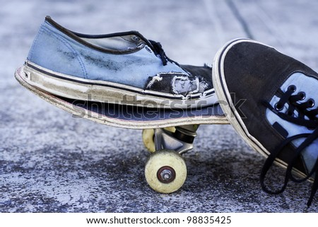 pair of worn out sneakers on a skateboard against concrete background - stock photo