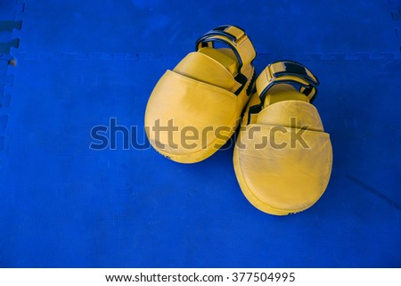 Pair of yellow boxing gloves hanging on a Blue wall - stock photo