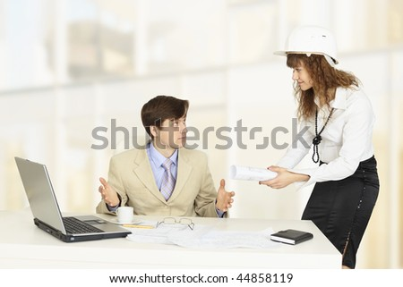 Pair of young engineers on a workplace